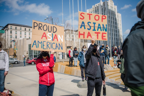 Two individuals hold signs protesting against Asian hate and supporting the Asian community at a gathering.